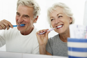 Happy Couple Brushing Teeth Side by Side | Toothbrush | Oral Health | Lake Cities Dental | Southlake, TX